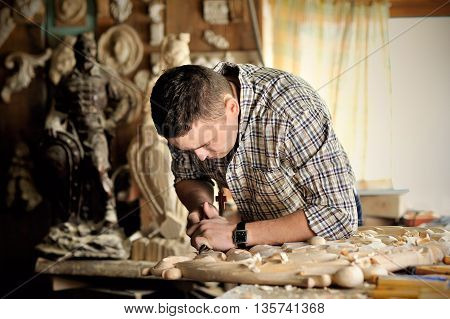 carver working art wood carving with chisel