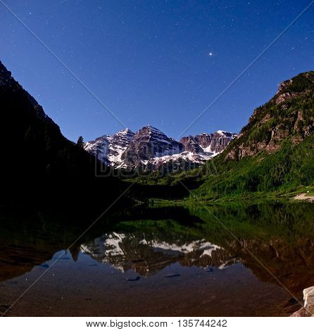 Crater Lake with reflection of Maroon Bells and starry sky at night.  Maroon Peak near Aspen and Snowmass, Colorado,  USA.