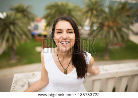 Happy smiling woman in white dress standing on villa terrace enjoying the summer holiday. Finding your inner peace.Smiling to problems concept.Paradise vacation,relaxation on a sunny day.