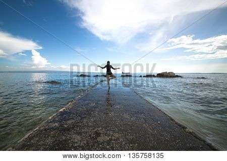 Woman doing yoga at the dock.Mindfulness state.Woman relaxing at the seaside dock in tree pose.
