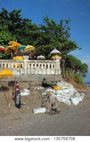 BALI INDONESIA - JUNE 23: A Balinese-Hindu seaside temple damaged by freak waves and severe coastal erosion is protected with sandbags on June 23 2016 at Batu Belig Beach Bali Indonesia.
