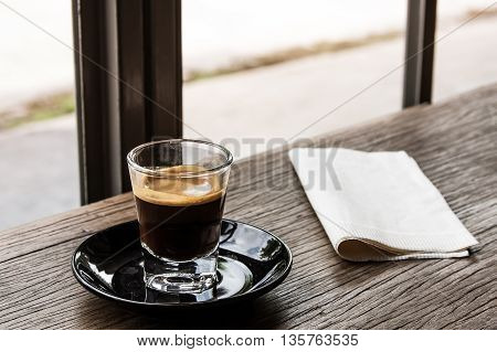 single shot espresso on wood table at coffee cafe with warm tone