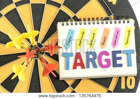 six dart in bullseye with words target on the notebook with handwriting timely achievable relevant goals education teamwork over dartboard background Business success concept