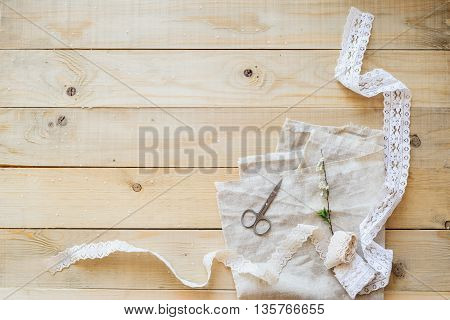 crafts concept lace ribbon and flowering branch on wooden table