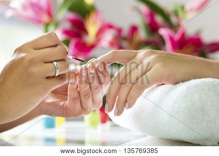 Woman in a nail salon Closeup shot receiving a manicure by a beautician with nail file. Woman getting nail manicure. Beautician file nails to a customer.