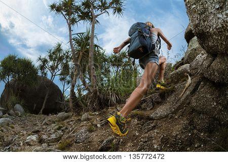 Lady hiker passing rocky terrain