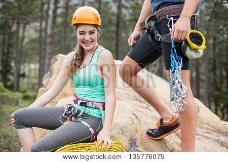 Portrait of happy woman with man sitting on rock at forest