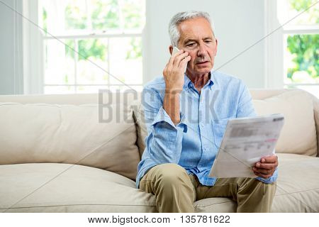 Old man reading document while talking on phone in living room at home