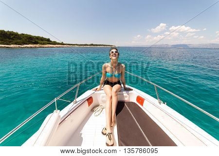 Beautiful woman standing on shipboard and getting ready to sail away to an open sea. Woman on her private boat on a sunny summer day. Luxury vacation at sea. Getting fascinated by sea life.Honeymoon