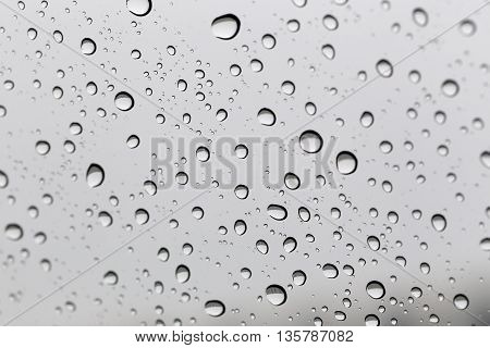 Drop of water for the background on glass car window to abstract design and nature backdrop.