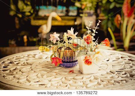 Artificial flower in the vase on the table in vintage