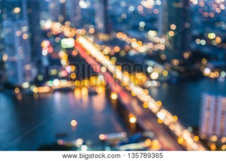Blurred bokeh lights aerial view city bridge cross river night view, abstract background