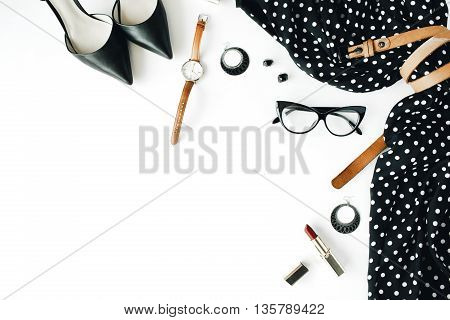 flat lay feminine clothes and accessories collage with black dress glasses high heel shoes purse watch mascara lipstick earrings on white background.