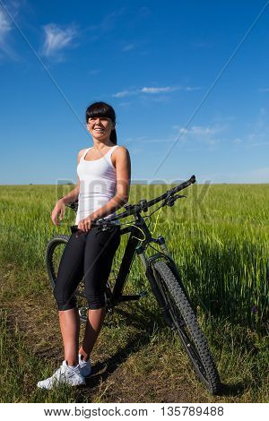Sport bike woman on a meadow with a beautiful landscape. Healthy lifestyle