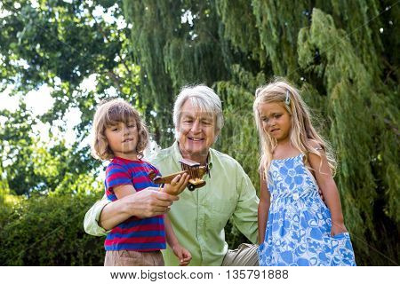 Grandfather playing with grandchildren at back yard