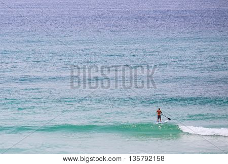 PENSACOLA BEACH, USA - MAY 13, 2015: A man doing standup paddleboarding in light surf close to the beach.