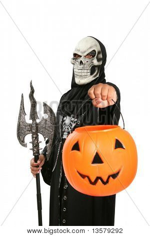 A boy in a scary halloween mask holding a pumpkin for candy