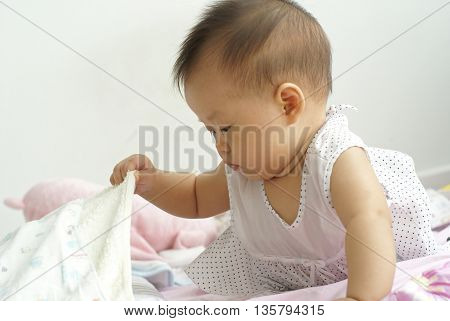 Cute infant finding something hidden under a blanket. Asian infant finding item under a blanket.