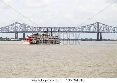 NEW ORLEANS, USA - MAY 14, 2015: Crescent City Connection over the Mississippi River with the Steamboat Natchez in the foreground.