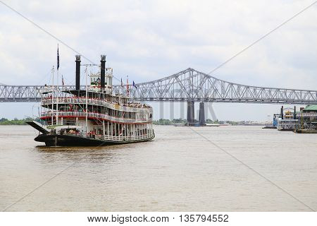 NEW ORLEANS, USA - MAY 14, 2015: Steamboat Natchez on the Mississippi River in the back the Crescent City Connection.