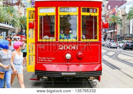 NEW ORLEANS, USA - MAY 14, 2015: Streetcar stopped on Canal Street two women with colorful wigs crossing the street in front of it.