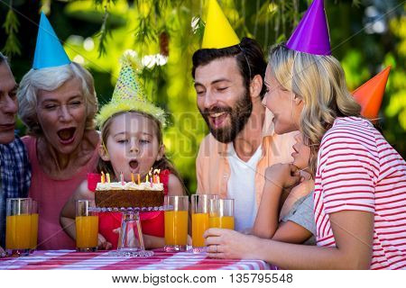 Happy family celebrating birthday with girl at yard