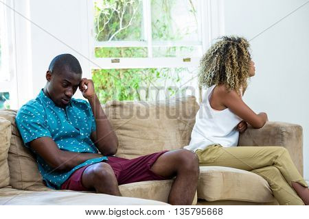 Upset couple sitting on sofa and ignoring each other at home