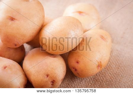 Potato tubers on a table close-up top view