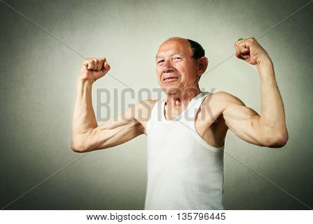 portrait of funny senior man showing the muscles