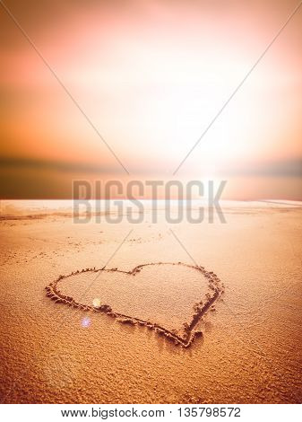 Love sign writing on sand at the sunset time, Love concept.