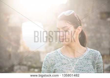 Natural young woman enjoying sunny day outdoors.Enjoyment and calming.Enjoying nature with eyes closed,breathing pure fresh air.Stress free concept.