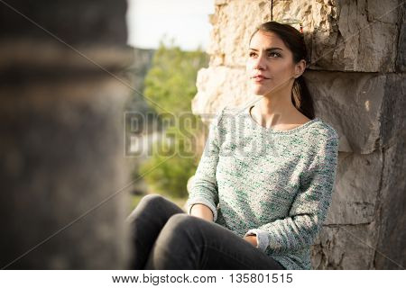 Thoughtful woman sitting alone outdoors.Daydreaming and imagining.Overcoming depression and anxiety problems.Optimistic person expression.Reflecting on past.Relaxing walk in nature.Stress relief