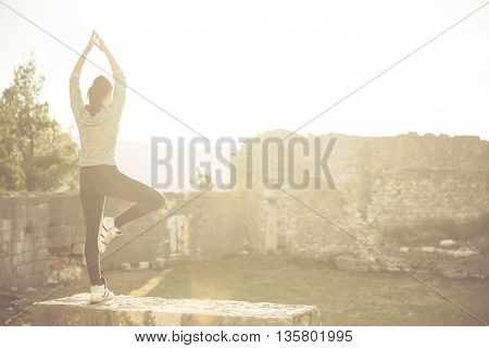 Yoga and meditation concept.Woman meditating in standing yoga position outdoors.Woman alone practicing mindfulness meditation to clear her mind.Zen,meditation,peace concept
