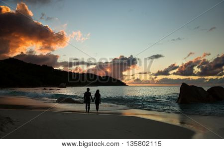 Sunset over the sea and beach, lover couple silhouette.