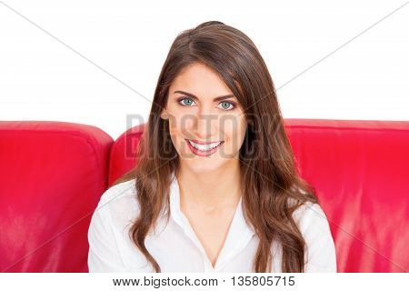 Portrait of young woman smiling. Attractive female with long brown hair is sitting on red sofa. She is with confident look on her face isolated on white background.