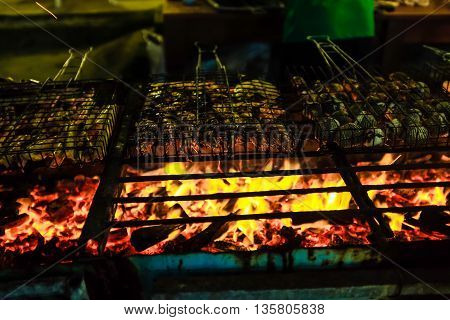 Row Delicious Prawn Fish And Shell On Grill With Flames