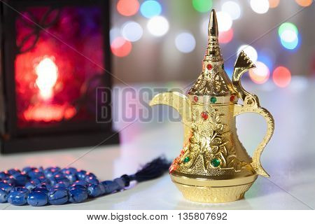 Arabic Coffee pot muslim prayer beeds and lantern with colorful out of focus light as background. Ramadan Eid concept background
