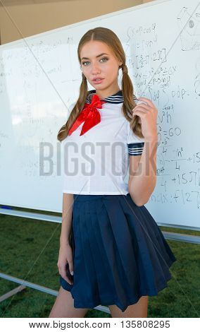 sexy naughty school girl in plaid skirt with attitude and showing side of breast