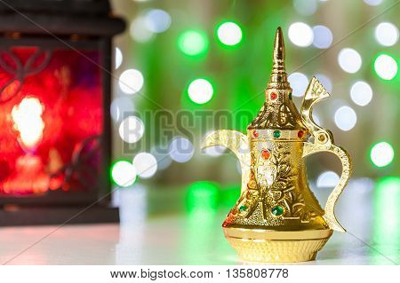 Gold Arabic Coffee pot in colorful illuminated background. Ramadan and Eid Mubarak concept background