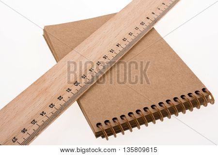 ruler and notebook placed on white background