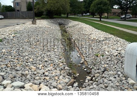 A drainage ditch holds water beside a parking lot in Shorewood, Illinois.