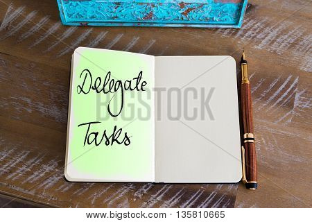 Handwritten Text Delegate Tasks over notebook, copy space available