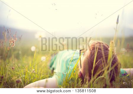 Carefree happy man lying on green grass meadow in mountains enjoying the sun on his face.Enjoying nature sunset.Freedom.Enjoyment.Relaxing in mountains at sunrise.Sunshine.Daydreaming
