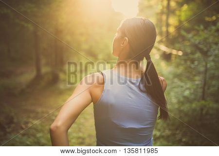 Runner woman jogging in the forest trail.Beautiful fit female fitness woman training and working out outside in summer as part of healthy lifestyle.Fitness woman running at sunset in woods