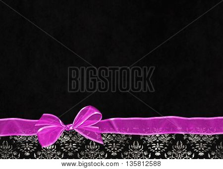 Bright pink bow with sheer ribbon on damask border and textured black background.