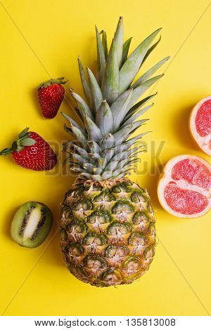 Overhead view of fresh pineapple and other fruits on yellow background. Top view concept shot of pineapple, strawberries, sliced kiwi and grapefruit. No retouch, no filter.