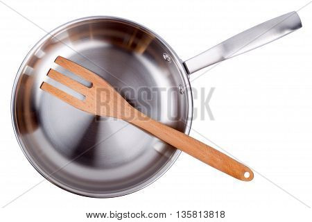 Steel frying pan and wooden scapula isolated on a white background. Top view