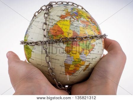 Hand holding a colorful globe in chains