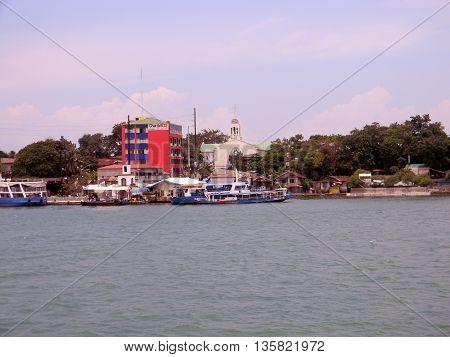 LAPU LAPU CITY, CEBU / PHILIPPINES - JULY 30, 2011: A view the shore of Lapu Lapu City, as seen from a passenger ferry departing the island of Cebu.