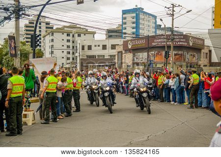 QUITO, ECUADOR - JULY 7, 2015: Three motorcycles helping pope Francisco with their security, police and people on the streets.